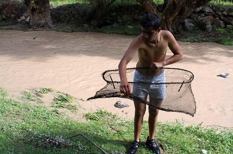 Мальчик ловит рыбы в реке Мелендыз.