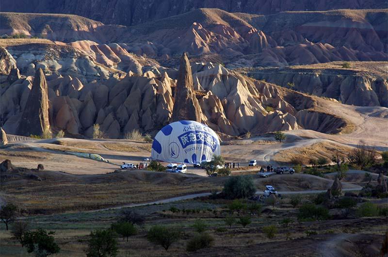 Наполнение воздушного шара горячим воздухом на площадке взлета.