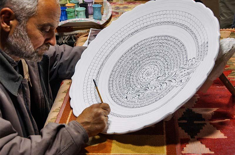 Художник расписывает необожженную керамику в мастерской в городе Аванос.