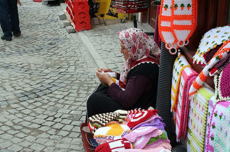 Женщина вяжет вещи на продажу.