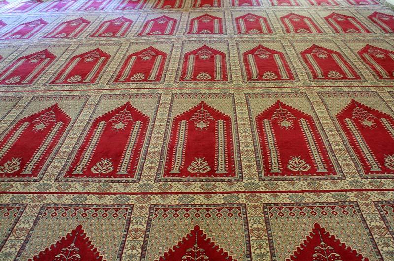 Ковер на полу, на котором нарисованы коврики для молитв.
