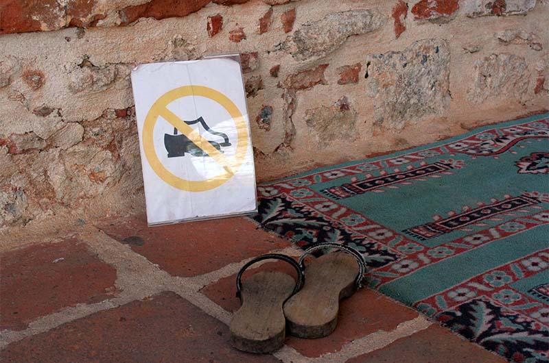 Напоминание о том, что перед входом в мечеть надо снимать обувь.