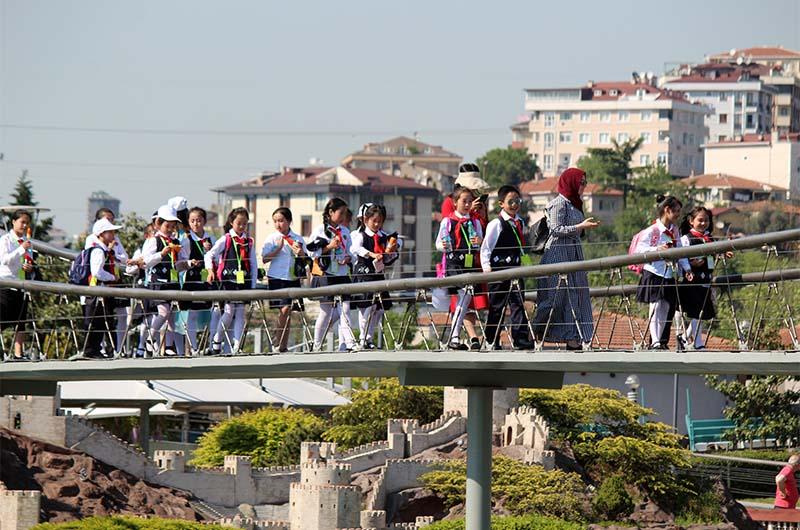 """Школьники на экскурсии идут по мосту через """"Пролив Босфор""""."""