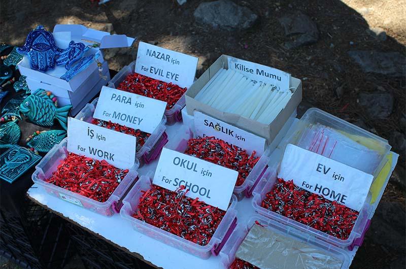 Рядом идёт бойкая торговля оберегами. На табличках написано: «Для денег», «Для работы», «Для школы» и т.п.