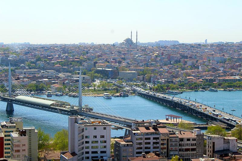 Это вид на залив Золотой Рог. На переднем плане вантовый мост Золотой Рог, по которому идут электрички метро. Правее находится мост Ататюрка. Мечеть на холме – очень известная мечеть Фатих.