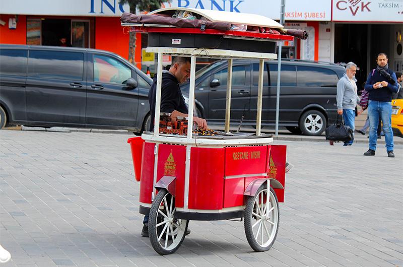 Продавец жареных каштанов на площади.